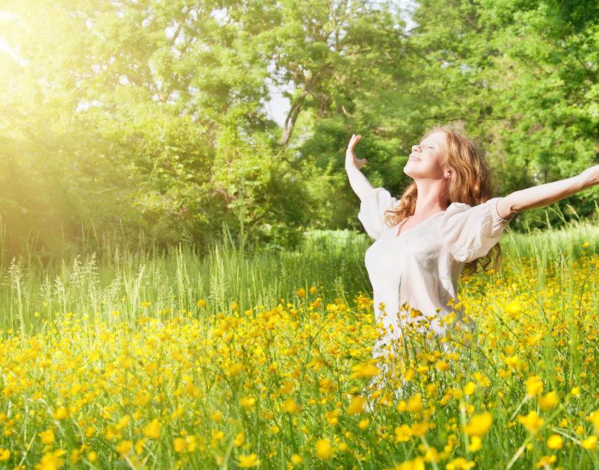 Access Consciousness - Frau steht in einem Feld und streckt die Arme aus