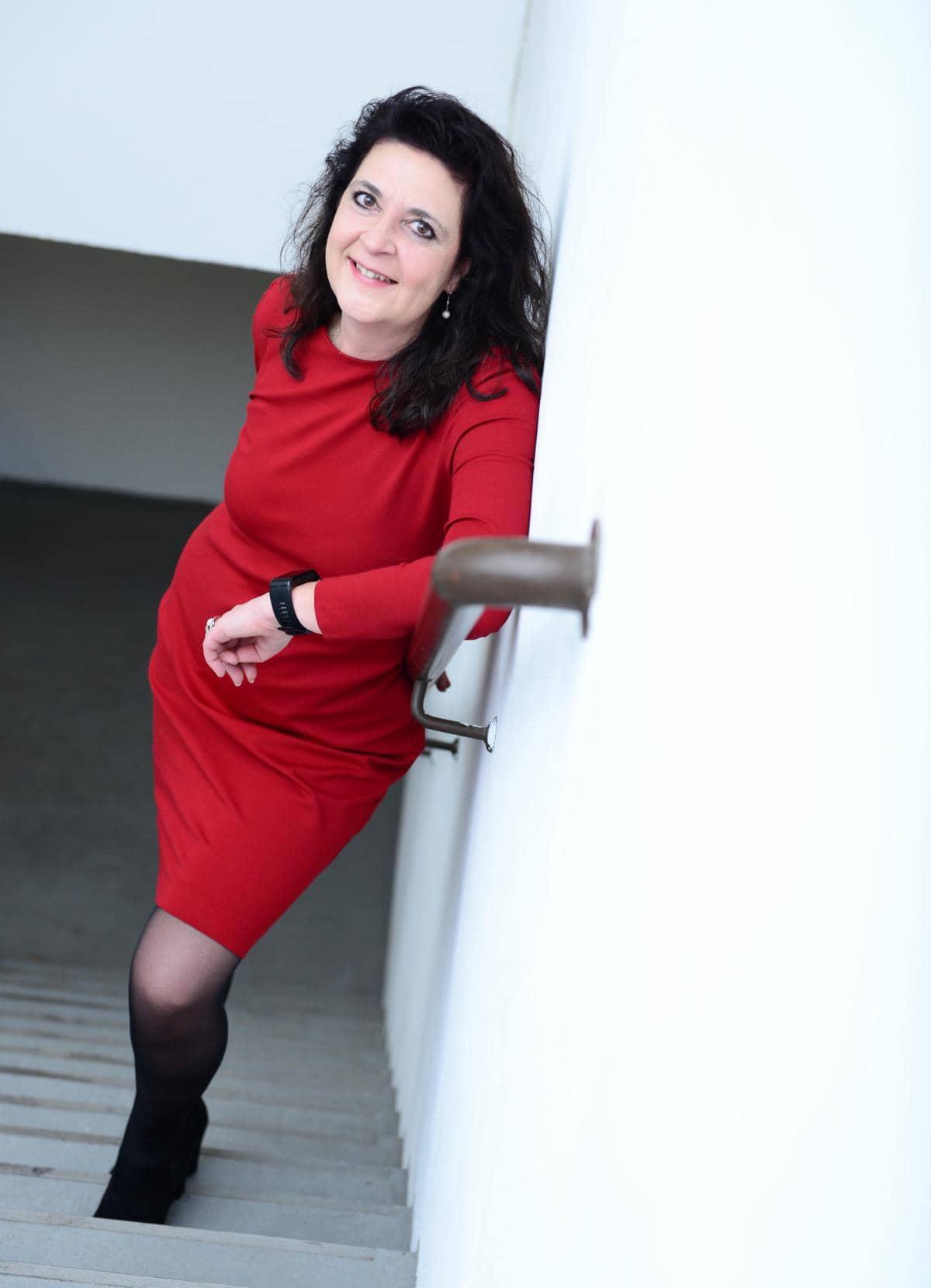 Sonja Giesen in rotem Kleid auf einer Treppe