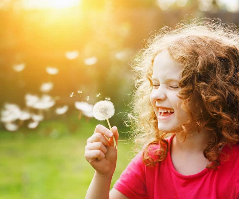 Access Consciousness - Lachendes Kind mit Pusteblume in der Hand